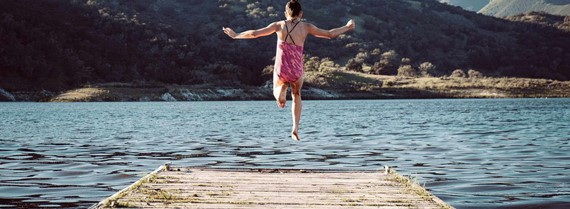 Image of girl leaping into a lake