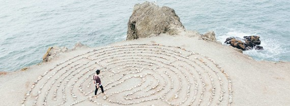 Image of person walking through a maze made of pebbles on a beach